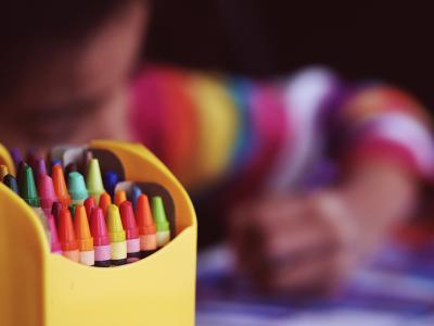 Child drawing with coloured pens